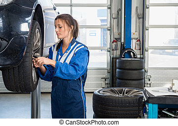 Mechanic Changing Tire From Suspended Car