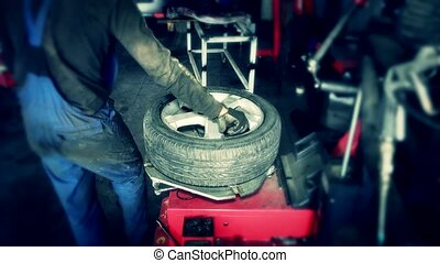 Mechanic changing tire in car service. Tire rotation...