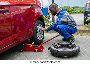 Mechanic Changing Tire With Wrench