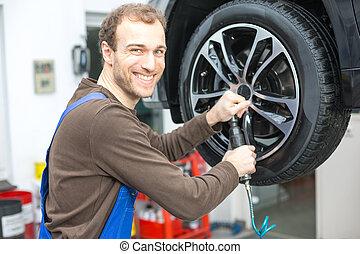 Mechanic changing wheels on a car on hydraulic ramp
