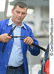mechanic changing windshield wiper blades on a car