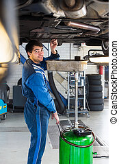 Mechanic chaning the oil of a car
