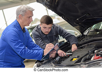 mechanic checked in the engine compartment of a car