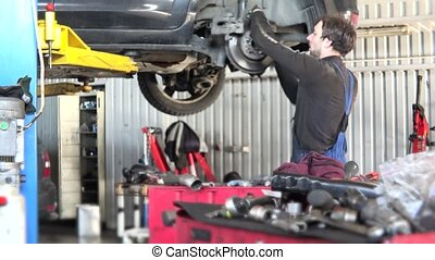 Mechanic checking car brake system in a workshop - Dirty...