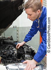 Mechanic checking car engine oil