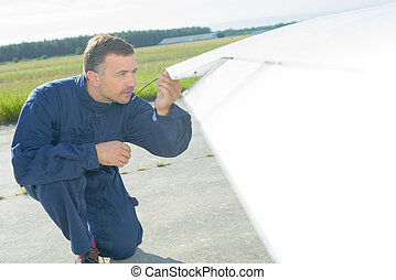 Mechanic checking wing tip of aircraft