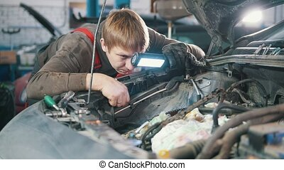 Mechanic checks and repairs automotive engine, car repair,...
