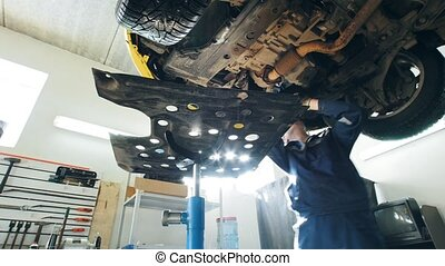 Mechanic checks the bottom of car in garage automobile service, close up