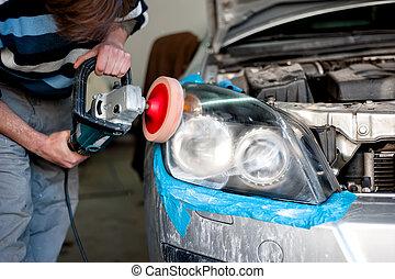 Mechanic cleaning headlights and polishing with power buffer