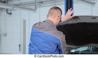 Mechanic closes car hood at the car service