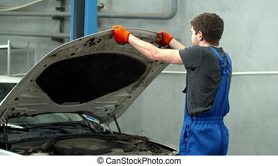 Mechanic closes hood of car and looks at the camera