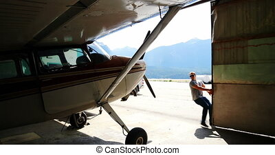Male mechanic closing hangar gate 4k