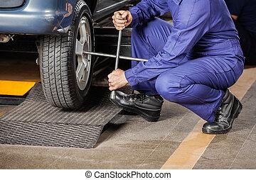 Mechanic Crouching While Fixing Car Tire