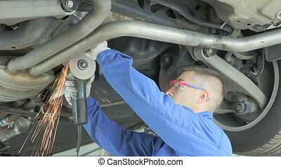 Mechanic cuts off the muffler in the car. Master in...