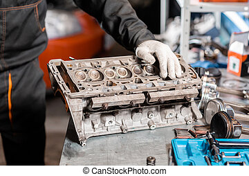 Mechanic disassembling the engine, overhaul.. Engine on a...