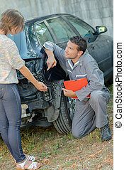 Mechanic discussing accident damage on a car with customer