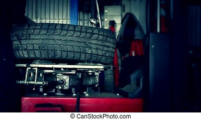 mechanic dismount tire from rim with special machine.