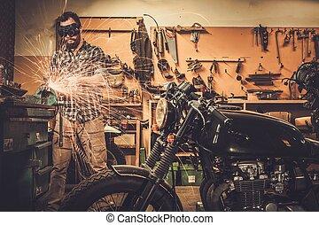 Mechanic doing lathe works in motorcycle customs garage