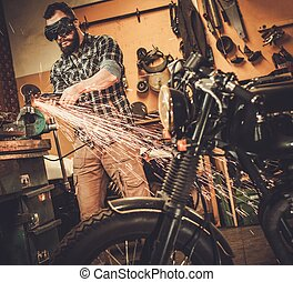 Mechanic doing lathe works in motorcycle customs garage