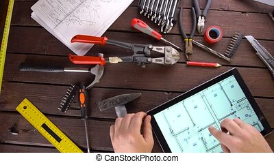Mechanic engineer works with tablet on his desk