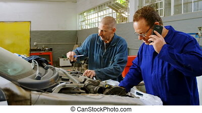 Mechanic examining a car while his colleague talking on mobile phone 4k