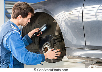 Mechanic Examining Brake Disc Of Car In Garage