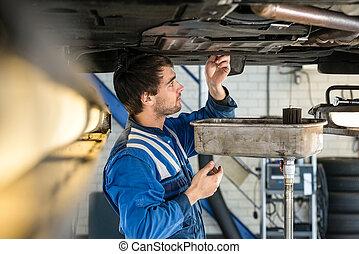 Mechanic Examining Car At Garage