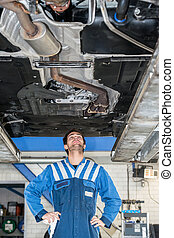 Mechanic Examining the state of an exhaust system Under The Car At Garage