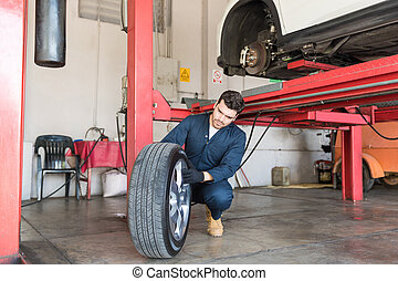 Mechanic Examining Tire For Replacement In Repair Shop
