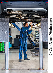 Mechanic Examining Under The Car At Garage