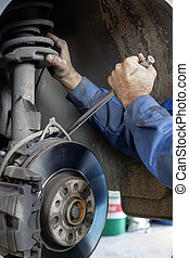 Hands mechanics repaired the brakes on a passenger car