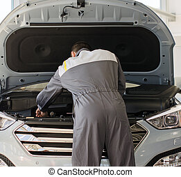 Mechanic fixes car in workshop.
