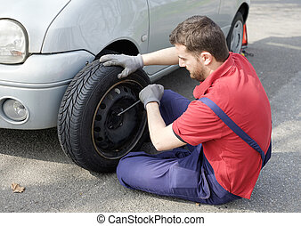 Mechanic fixing a car problem after vehicle breakdown on the road