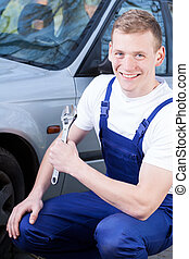 Mechanic fixing car and smiling