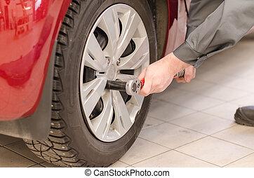 Mechanic fixing car wheel at service.