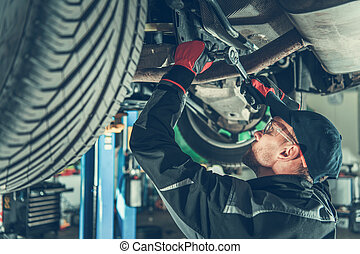 Mechanic Fixing Chassis Of Car In Garage.