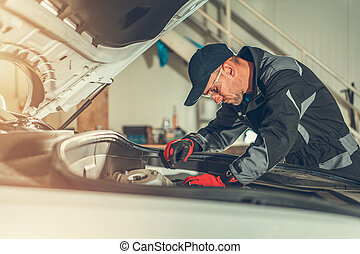 Mechanic Fixing Components Under Car Hood.