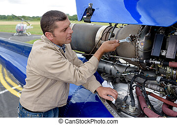 mechanic fixing the motor of a plane