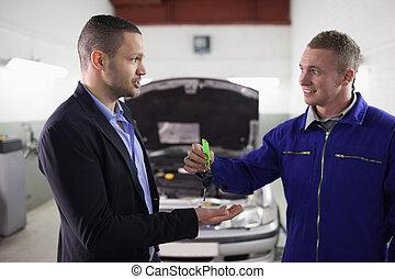 Mechanic giving car key to a man