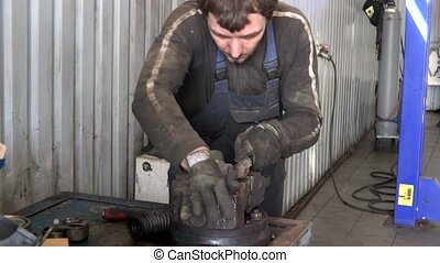 mechanic guy grind rusty metal with rasp tool in garage.