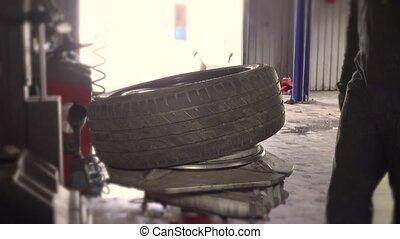 mechanic guy in dirty work wear mounting tire on wheel rim.