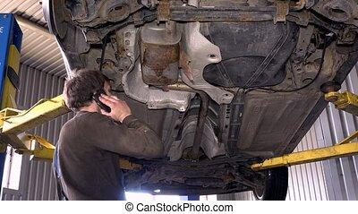 Mechanic guy with phone repairing rusty exhaust system.