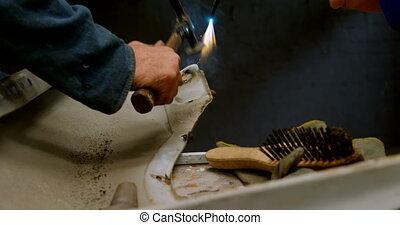 Mechanic hammering car part at repair garage 4k - Close-up ...
