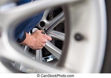 Mechanic hands at a tire service center - Mechanic changing...