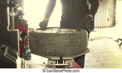 Mechanic hands repairs a tire.