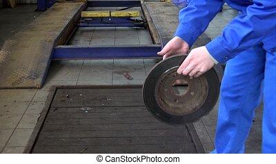 mechanic hands showing worn rusty brake disk at garage.