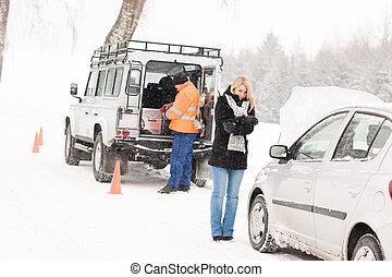 Mechanic helping woman with broken car snow