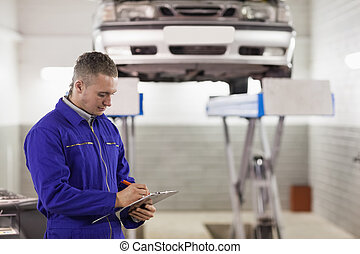 Mechanic holding a clipboard while looking at it in a garage