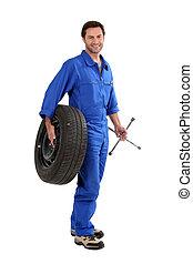 mechanic holding a tire
