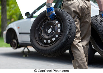 Mechanic holding a two car wheel